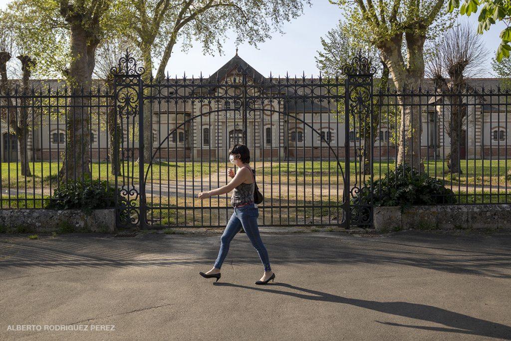 """Une passante """"masquée"""" devant la grille fermé des anciens Haras de Blois."""