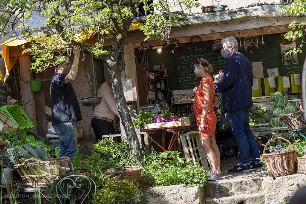 """Un couple masqué fait ses course à l'épicerie bio """"Le petit jardin""""."""