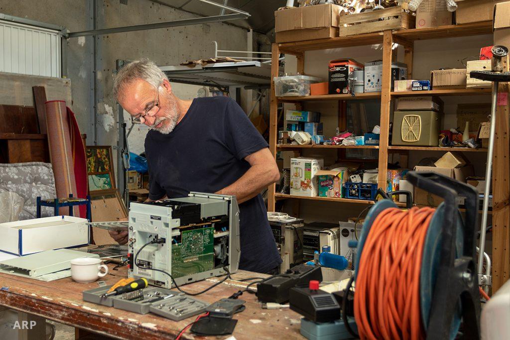"""Un bénévole répare un ordinateur à la Ressourcerie """"Les Bonnes Manières"""" à Blois"""