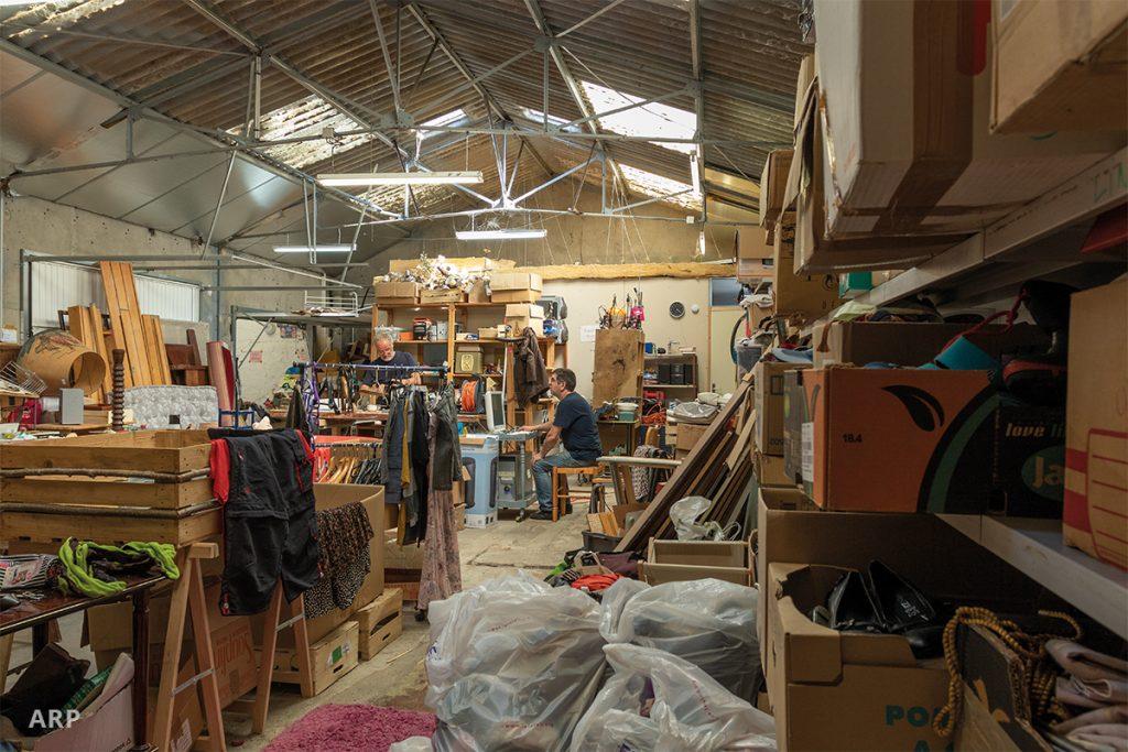 L'entrepôt de la ressourcerie entasse des milliers d'objets que des bénévoles s'apprêtent à nettoyée avant de les mettre en vente.