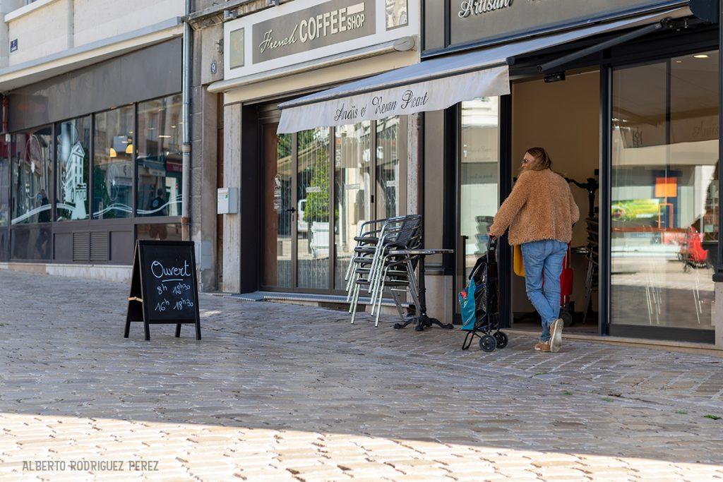 Une femme attend patiemment son tour à l'extérieur de la boulangerie.